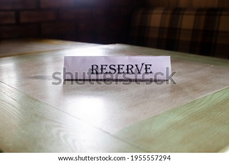 The flying around the plate is reserved, which stands on the wooden table in the restaurant. Reservation of a place in the cafe. Seat reservation. Reserving a table in the institution in advance. Royalty-Free Stock Photo #1955557294