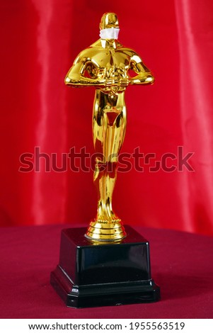 Hollywood Golden Oscar Academy award statue in medical mask on red background. Success and victory concept. Oscar ceremony in coronavirus time