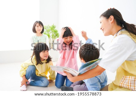 Nursery teacher and children reading a picture book