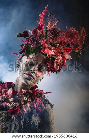 A girl smeared with clay. The model has a headdress made of flowers. Royalty-Free Stock Photo #1955600416