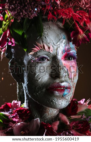 A girl smeared with clay. The model has a headdress made of flowers. Royalty-Free Stock Photo #1955600419
