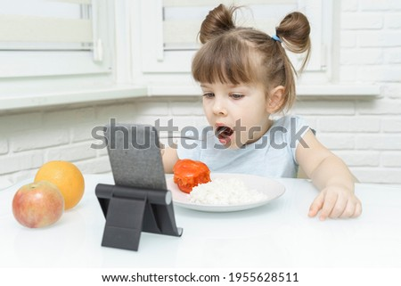 kid girl eating food and watching cartoons on a smartphone