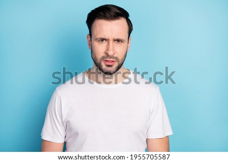 Portrait of attractive moody discontent suspicious guy wearing white tshirt isolated over blue bright pastel color background