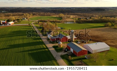 American midwestern countryside in springtime. Aerial view of farms with red barns in spring, rural road, agricultural fields Royalty-Free Stock Photo #1955728411