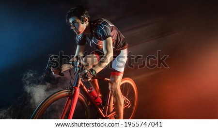Sport. Athlete cyclists in silhouettes on dark background Royalty-Free Stock Photo #1955747041