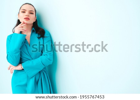 High fashion portrait of young beautiful brunette woman wearing nice trendy summer dress.Sexy fashion model posing near light blue wall in studio.Fashionable female indoors