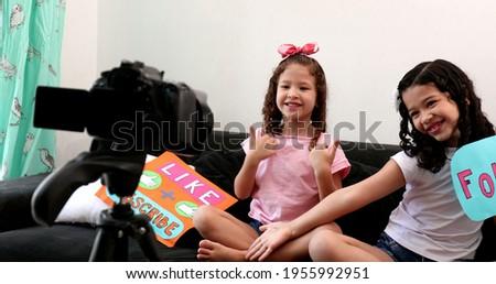 Children talking to camera building social media presence, two little girls vlogging