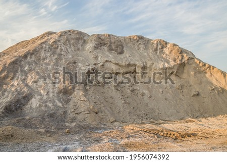 Stock of inert building materials. A mountain of sand and gravel mixture against the sky.High resolution photo.