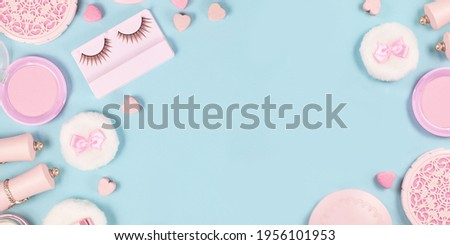 Banner with cute pink makeup beauty products like brushes, powder or lipstick on sides of pastel blue background with empty copy space in middle