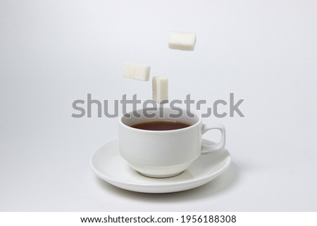 Sugar cubes fall into a cup of tea on a white background. A cup of tea with refined sugar. Tea time