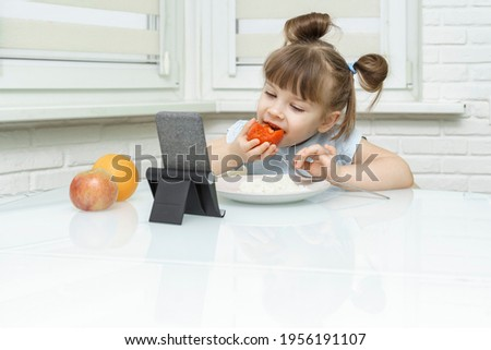 kid girl eating food and watching cartoons on phone. a way to feed your baby healthy food