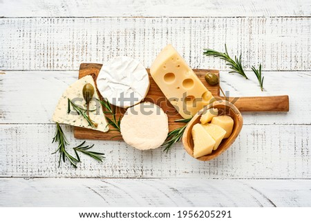Set or assortment cheeses. Suluguni with spice, camembert, blue cheese, parmesan, maasdam, brie cheese with rosemary and pepper.  Top view. On white wooden old background. Free copy space. Royalty-Free Stock Photo #1956205291