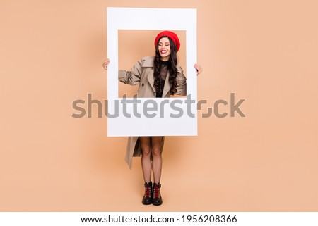 Full size photo of attractive charming girl wear pantyhose hold photo frame isolated on beige color background