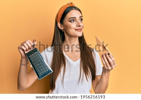 Beautiful brunette young woman holding grater and cheese smiling looking to the side and staring away thinking.