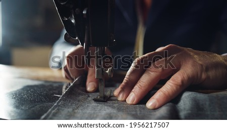 Macro shot of experienced tailor is sewing custom handmade high quality apparel in ancient luxury traditional tailoring workshop. Concept of industry, handmade, hand craft, couturier and tradition. Royalty-Free Stock Photo #1956217507