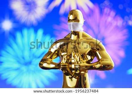 Hollywood Golden Oscar Academy award statue in medical mask on fireworks background. Success and victory concept. Oscar ceremony in coronavirus time