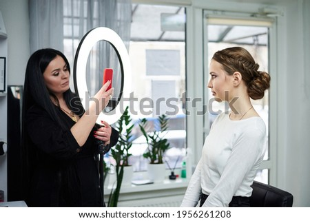 Professional make-up artist taking picture of work result with her phone, using ring light. Work process in beauty salon. Close-up picture on make-up model. Bride getting ready for wedding.