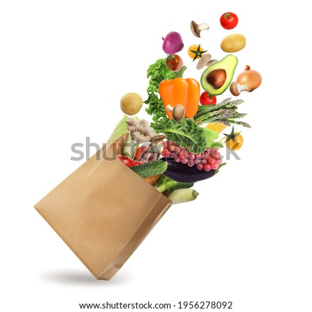 Paper bag with vegetables and fruits on white background. Vegetarian food  Royalty-Free Stock Photo #1956278092