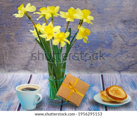 Bouquet of yellow daffodils in a glass vase, a gift box, a cup of coffee and a plate with pancakes on the wooden background. Painted picture effect.