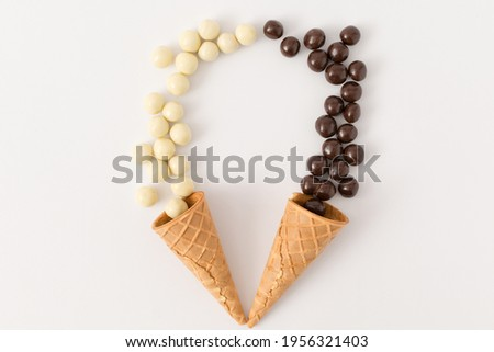 Cornet and contrast between black and white chocolate balls. Minimal flat lay. Royalty-Free Stock Photo #1956321403