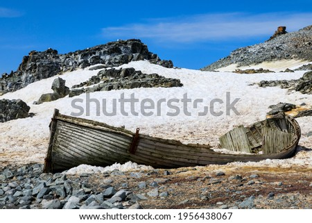 Historical old wooden boat abandoned and dilapidated on the rocky icy shore of Half Moon Island in the South Shetland Islands of Antarctica Royalty-Free Stock Photo #1956438067