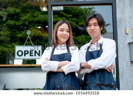 Two Asian barista or coffee maker man and woman stand with arm-crossed or confidence action also look to camera and smile in front of coffee shop. Concept of happy working with small business.