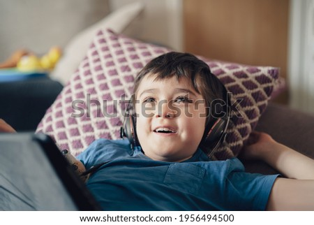 Happy kid wearing headphone looking up watching cartoon TV, Smile boy lying on sofa listening music on Tablet, Child with smiling face having fun playing games at home. New normal life style