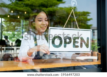 Barista or coffee maker woman hold banner of open for the symbol of ready to service for customer. Concept of happy working with small business and sustainable.