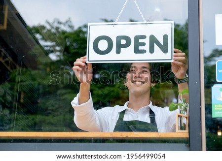 Barista or coffee maker man hold banner of open for the symbol of ready to service for customer. Concept of happy working with small business and sustainable.