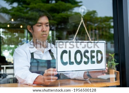 Barista or coffee maker man hold banner of closed for the symbol of no service for customer. Concept of virus pandemic and effect to people.