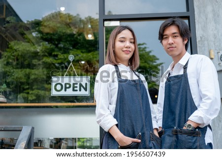 Two Asian barista or coffee maker man and woman stand with confidence action also look at camera and smile in front of coffee shop with day light.