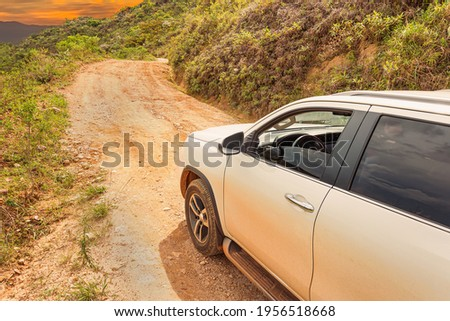 SUV car going up the sierra on a rocky road, white car on sloping ground during sunset.  Concept of eco tourism 4x4 adventure. Brazilian sierra of the Minas Gerais state. Royalty-Free Stock Photo #1956518668