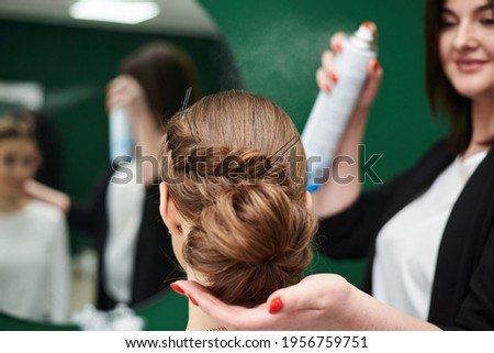Bride getting ready for wedding. Professional hairdresser making coiffure for female client, applying hairspray in front of big mirror. Work process in beauty studio. Close-up picture of gala hairdo.