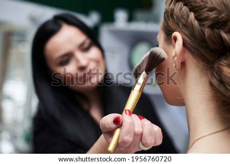 Bride getting ready for wedding. Professional make-up artist applying blush on female clients' face with big makeup brush. Work process in beauty studio. Close-up picture on make-up model.