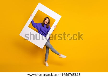 Photo of adorable charming young woman wear purple sweater dancing holding white photo frame isolated orange color background