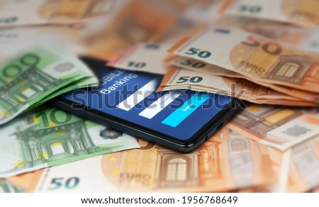 Mobile banking and finance concept: smartphone with stock exchange market application, euro banknotes. Business background. Blurred concept Royalty-Free Stock Photo #1956768649