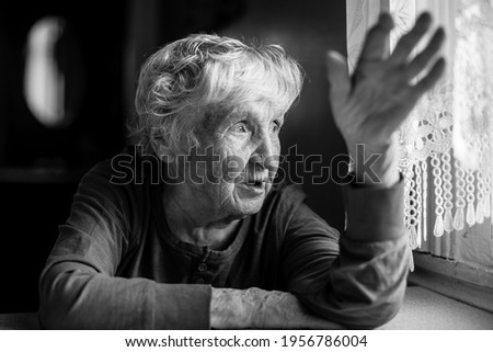 The old woman talking gesticulating at the table in her home. Black and white photo.