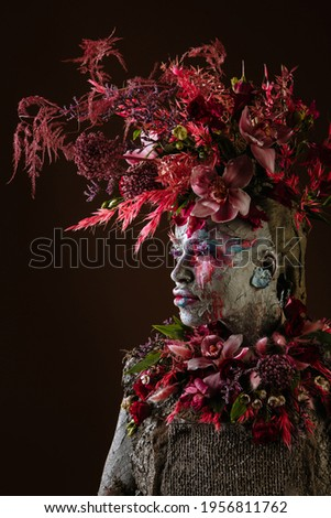 A girl smeared with clay. The model has a headdress made of flowers. Royalty-Free Stock Photo #1956811762