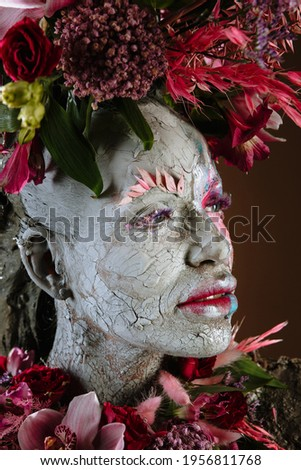 A girl smeared with clay. The model has a headdress made of flowers. Royalty-Free Stock Photo #1956811768