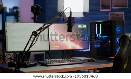Empty streaming home studio equipped with professional equipment during online tournament late at night in gaming studio. Pro streamer playing space shooter video game having esport championship Royalty-Free Stock Photo #1956819460