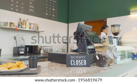 Smiling happy young Middle East woman waitress people wearing apron turning store from close to open sign, cafe cashier waitress at the coffee shop. People lifestyle. Business service.