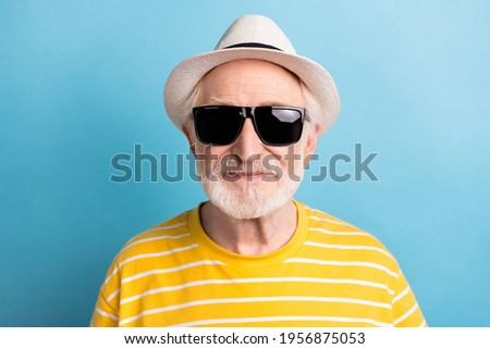 Close-up portrait of attractive cool man wearing black sun specs isolated over bright blue color background Royalty-Free Stock Photo #1956875053