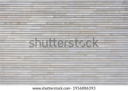 New light gray wood paneling made of narrow horizontal boards on a facade Royalty-Free Stock Photo #1956886393