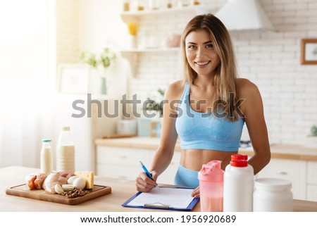 Waist-up photo of smiley young woman taking notes while standing in kitchen near food supplement containers and some products