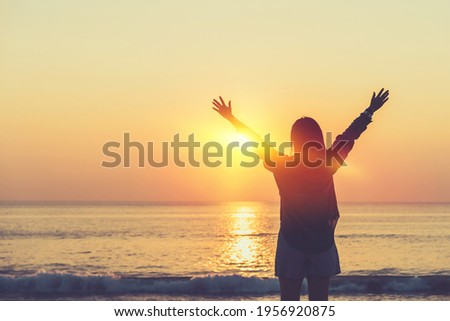 Copy space of woman rise hand up on sunset sky at beach and island background. Freedom and travel adventure concept. Vintage tone filter effect color style. Royalty-Free Stock Photo #1956920875