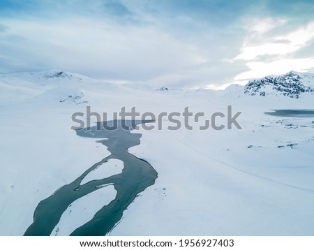 Stunning aerial view of a river flowing through a snow covered tundra and mountain range. Royalty-Free Stock Photo #1956927403