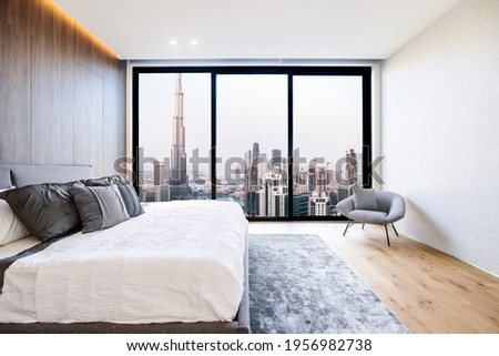 Modern and luxurious bedroom with white ceiling and wood accents with views of Burj Khalifa and downtown Dubai skyline. Condo or Hotel accomodation. Royalty-Free Stock Photo #1956982738