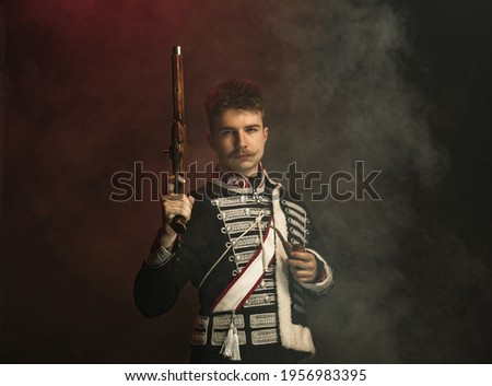 Duelist. Young man in suit as royal person isolated on dark green background. Retro style, comparison of eras concept. Beautiful male model like historical character, monarch, old-fashioned. Royalty-Free Stock Photo #1956983395