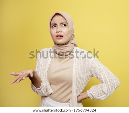asian hijab women talk asking. confuse expression. isolated on a yellow background Royalty-Free Stock Photo #1956994324