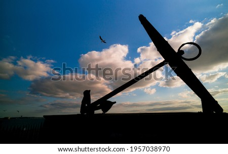 HMS Victory anchor with flying birds. Same shape picture. Blue sky and white clouds. Portsmouth, UK.